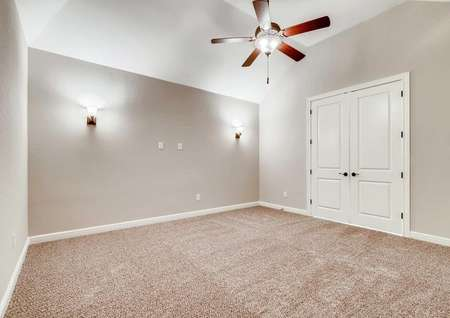 Timberline bedroom with French doors, dark brown ceiling fan, and light color carpeting