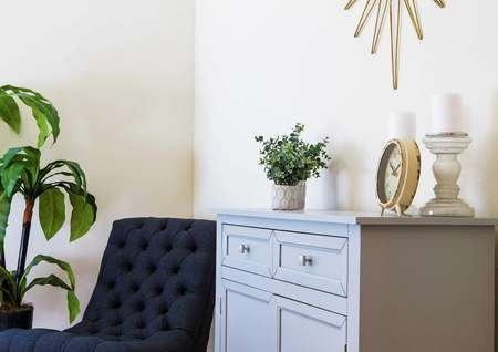 Staged model with a clock on a desk, plants, and a dark blue chair in the Maple floor plan