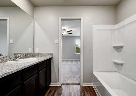 Carson bathroom with white shower and bathtub combination, granite vanity with gray color, and brown cabinets