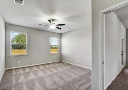 Fannin completed bedroom with brown carpeting, with white baseboards, and two white framed windows