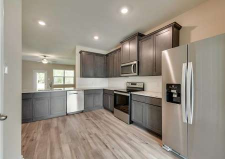 The kitchen in the Texoma floor plan with recessed lighting, stainless steel appliances and modern wood cabinets.