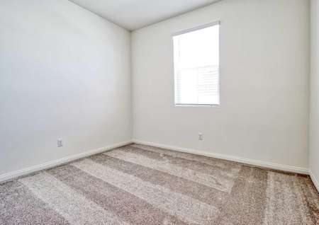 A bedroom in the Jasmine floor plan with white walls, white baseboards and light brown carpet flooring.