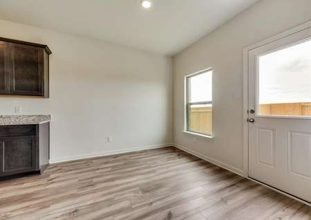The dining room has back yard views and gorgeous wood-style flooring.