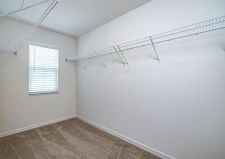 A large walk-in closet with a window is connected to the master bedroom.