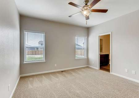 Arapaho bedroom with light color carpet, brown ceiling fan, and private bath
