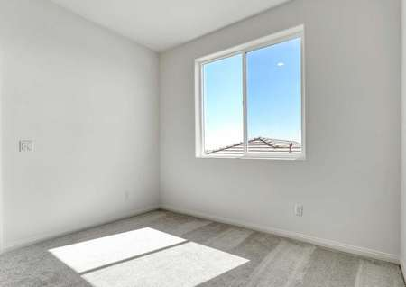A spare bedroom in the Sunflower floor plan with a large window, carpet flooring and multiple wall outlets.