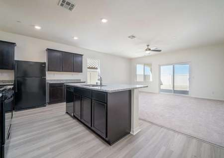Kitchen in the Del Mar floor plan with dark brown cabinets, wood-like floors, an island and a view of the living room.