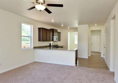 Living room with carpet looks into kitchen with granite breakfast bar and foyer with plank flooring.