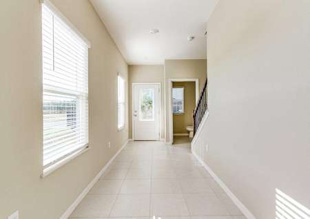 A hallway in the St. Johns floor plan with two windows, aview of the downstairs bathroom and the from door.