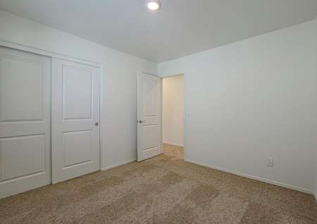 Guest bedroom with tan carpet and a closet with sliding doors.