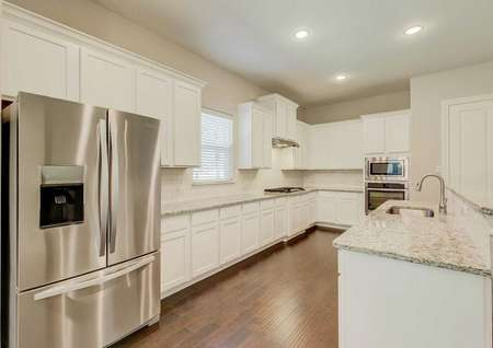 Fairview kitchen with recessed lights, white cabinets, and stainless steel appliances