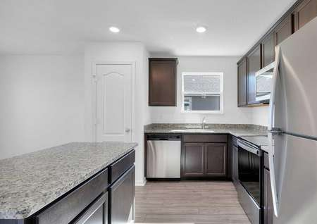 Angled view of kitchen appliances such as the refrigerator, dishwasher, microwave and stove.