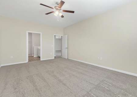 Carpeted master bedroom with a ceiling fan and a full bathroom.