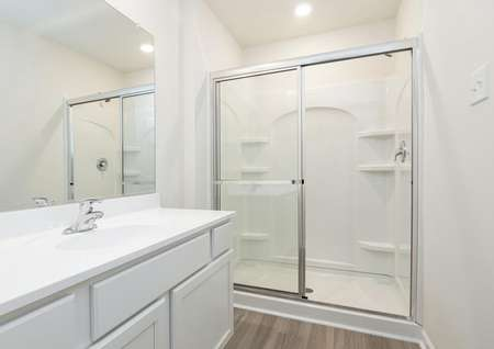 Owner bathroom with sprawling quartz vanity, single sink, extra-wide shower with glass sliding doors, recessed light and plank floor.