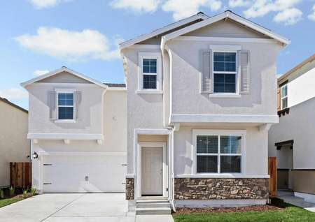 Stunning stucco and stone exterior home with charming window shutters.