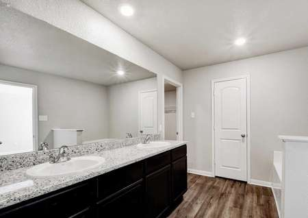 Shelby bathroom with granite counters, large mirror, and dark wood cabinet space