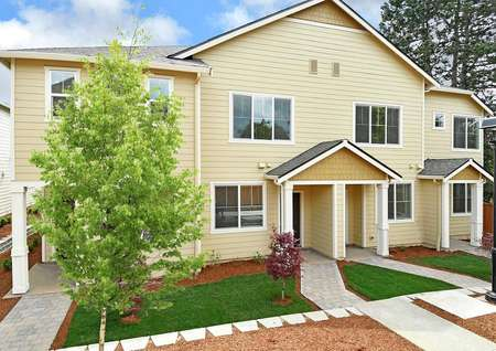 Photo of exterior of 4-unit townhome building includes, from left to right, Apple-Blackberry-Blackberry-Cherry floor plans, when looking at the front of the homes.