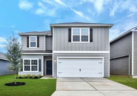 Travis finished house with two stories, grey siding with dark grey shutters, and white two car garage