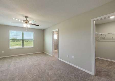 The master bedroom in the Tuscany floor plan that has a view of the walk-in closet and the master bathroom.