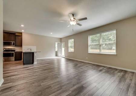 Saint Clair great room with brown walls with white baseboards, large backyard windows, and white backyard door with glass window