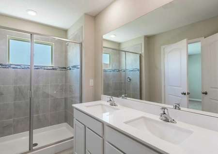 Sorrento bathroom with walk-in shower, dual sink vanity, and white cabinetry