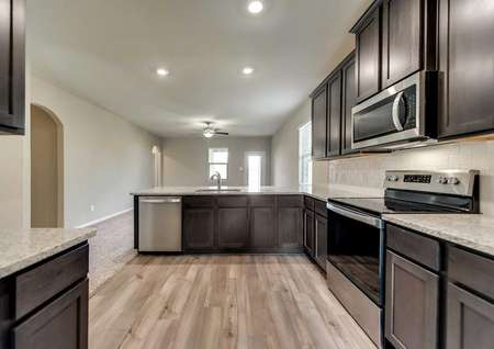 Maple kitchen completed with modern stainless steel appliances, dark wood cabinets, and overhead recessed lights