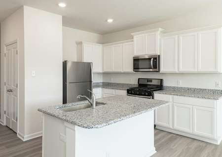 Close up of kitchen with white cabinets, gray granite counters, island with undermount sink, stainless appliances.