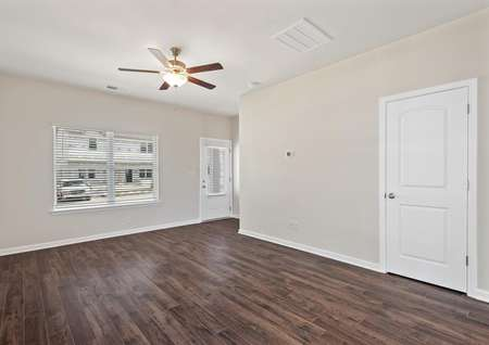 The family room has dark wood-style flooring and a ceiling fan.