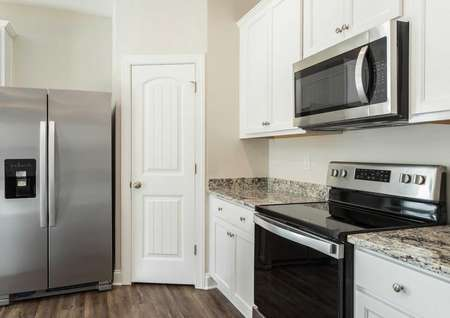 Avery kitchen with dual-door stainless steel refrigerator, granite counters, and walk-in pantry