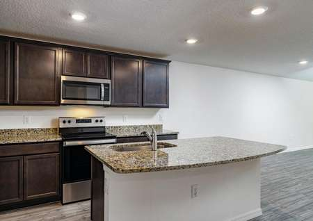 A chef-ready kitchen containing granite countertops and brand-new stainless steel appliances.
