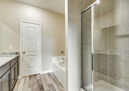 Master bath with a soaker tub, glass enclosed shower and brown cabinetry.