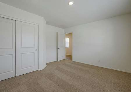 Guest bedroom with tan carpet and closet with sliding doors.