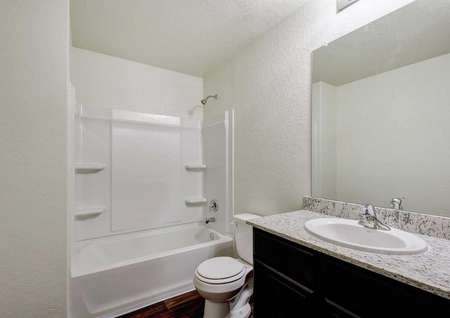 Mesquite bathroom with granite counter, white fixtures, and large mirror