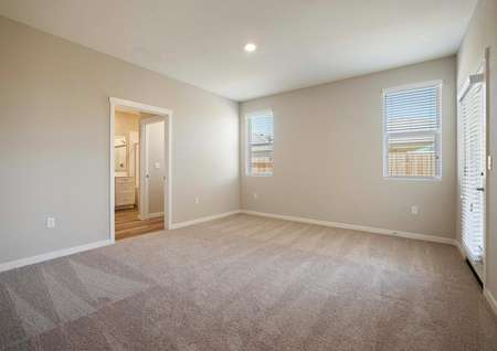 The spacious master suite has light brown carpet, tan walls and access to the master bath.