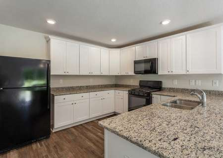 Fripp kitchen with black refrigerator, granite countertops, and white cabinets