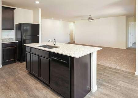 The Roosevelt floor plan kitchen shown with a granite island and vinyl wood flooring.