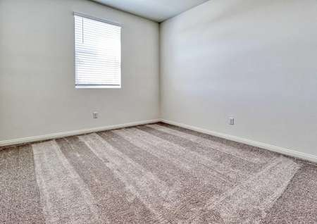 A spare bedroom in the Rosebud floor plan with a window covered by binds, brown carpet, white baseboards and white walls.