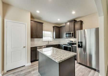 Erie kitchen with granite counters, food prep island, and stainless steel appliances