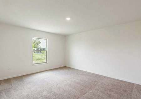 Bahia floor plan's spacious master bedroom with light brown carpet, white walls, a window and ceiling light fixture.