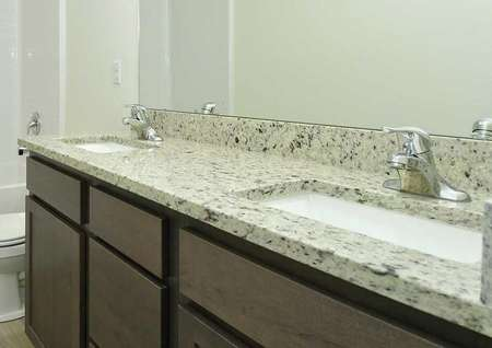 Hawthorn bathroom with two sinks, granite counters, and brown cabinets