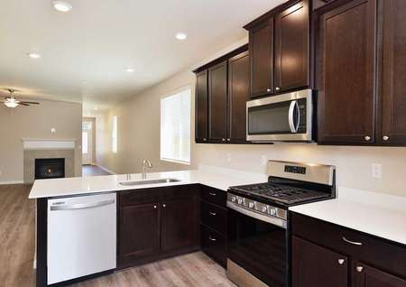 The Northwest Aspen side view of the kitchen showing dark brown kitchen cabinets with white quartz countertops.