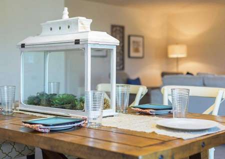 Home with wooden dining table that has place settings, tablecloth and a white decorative box on top.