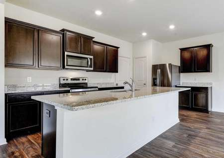 Rio kitchen with granite countertops, wood cabinets, and modern stainless steel appliances