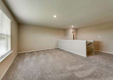 Game room with tan walls, white trim and brown carpet.