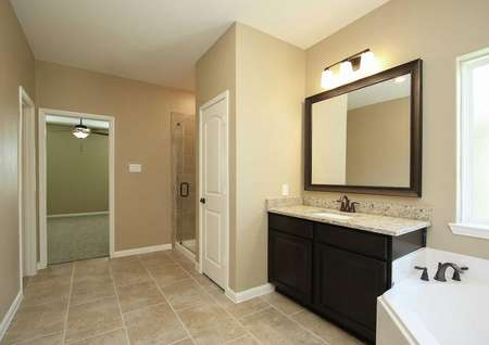 Master bathroom with tile flooring, dark cabinets, granite counters, drak framed mirror, decorative light fixture, frameless glass shower, soaker tub and view into bedroom with ceiling fan.
