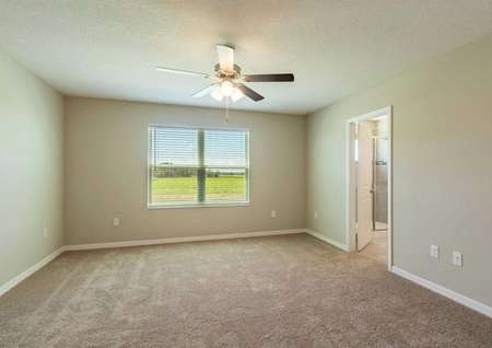 The Sorrento floor plansmaster bedroom that has a large window that is covered by blinds, carpet floors and tan walls.