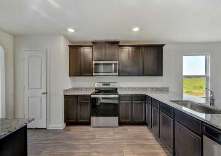 Frio kitchen with stainless steel stove and microwave, brown cabinets, and recessed light
