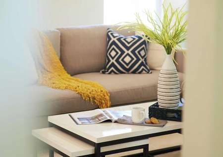 Staged home with sofa and navy pillow, yellow throw, coffee table and vase.