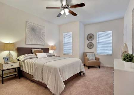 Fully furnished master bedroom with carpet flooring, two windows and a ceiling fan.