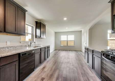 Whichita kitchen with wood finish floors, dark brown cabinetry, and black appliances